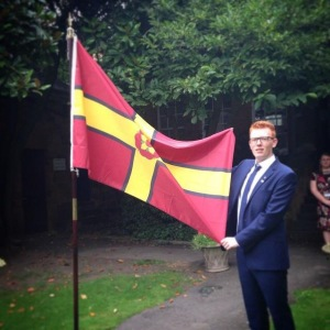Designer Brady Ells stands proudly beside the Northamptonshire flag.